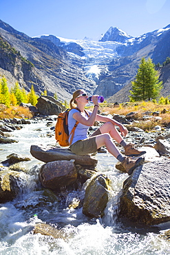 A female hiker relaxing near a river in the Swiss Alps. The region of Wallis, close to Zermatt. In the background is the Ried glacier. This valley is a paradise for outdoor enthusiasts like climbers, alpinists, hikers, mountainbikers and nature lovers. The water is directly coming from the glacier, so very refreshing after an excercise.
