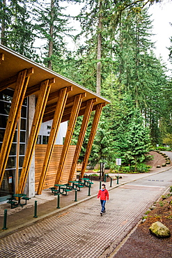 A man in red coat and jeans, walks beside a modern visitors center in a forested park.