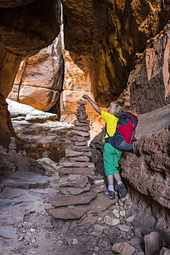 A young girl  backpacking past stone cairns on the Joint Trail in the Needles District of Canyonlands National Park, Monticello, Utah.