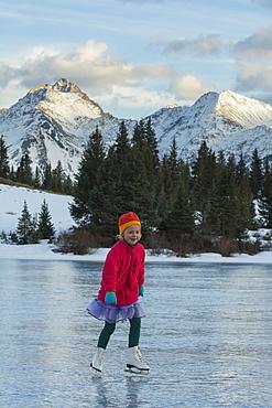A girl ice skating on early season ice, Molas Lake, San Juan National Forest, Silverton, Colorado.