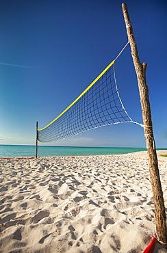 Two rough sticks hold up a beach volleyball net set up beside the ocean on Playa La Jaula beach, Cayo Coco, Cuba.