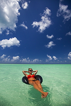 A young woman wearing a bikini relaxes on an inflatable tube in turquoise water while on vacation in Cayo Coco, Cuba.
