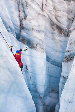 A man swings his ice tools as he climbs out of a moulin on a day trip with St. Elias Alpine Guides to the Root Glacier in Wrangell-St. Elias National Park, Alaska.