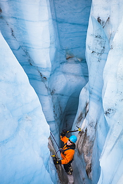 A woman swings her ice tools as she prepares to climb out of a moulin on a day trip with St. Elias Alpine Guides to the Root Glacier in Wrangell-St. Elias National Park, Alaska.