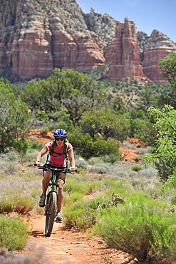 Woman rides the Templeton Trail in South Sedona, Arizona.  Templeton Trail rides over slickrock of the Cathedral Rock with views of Courthouse Butte across the way.