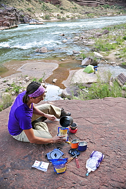 Female hiker cooks dinner on a cliff-pinched patio above camp and the Colorado River near Deer Creek Falls in the Grand Canyon outside of Fredonia, Arizona November 2011.  The 21.4-mile loop starts at the Bill Hall trailhead on the North Rim and descends 2000-feet in 2.5-miles through Coconino Sandstone to the level Esplanada then descends further into the lower canyon through a break in the 400-foot-tall Redwall to access Surprise Valley.  Hikers connect Thunder River and Tapeats Creek to a route along the Colorado River and climb out Deer Creek.