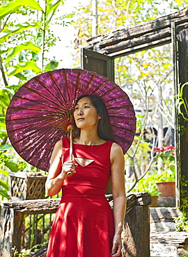 Beautiful woman in red dress at traditional Thai House