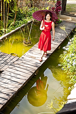 Beautiful woman in red dress walking through a Thai garden