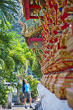 Woman admiring buddhist temple in Mae On in Northern Thailand