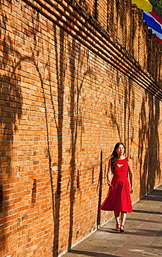 woman in red dress walking at the old city wall in Chiang Mai in northern Thailand