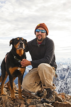Portrait of a man and his dog on the summit of Frosty Peak, BC, Canada.