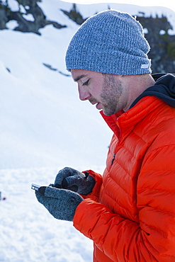 A climber checks his e-mail on his smartphone while camping in the mountains of British Columbia, Canada.