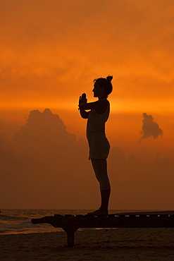 Girl doing yoga at sunset on the beach in Sri Lanka