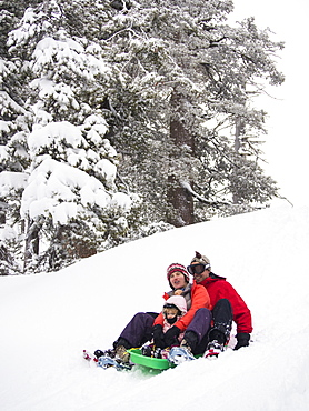 Parents and kids sledding in fresh snow in front of the Peter Grubb ski hut, Sierra Nevada