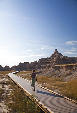 A young woman walks along a boardwalk in Badlands National Park, SD, United States of America