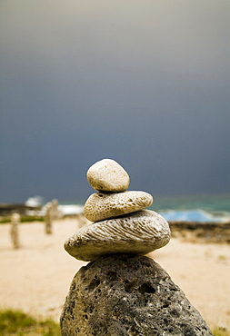 Stacks of rocks are placed on a beach for good luck under a threatening sky, Jamaica