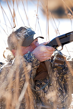 Corey Funk aims his shotgun while hunting duck in Carson City, NV, United States of America