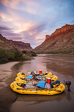 Inflatable rafts sit on the shore at sunset along a river.