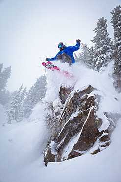 A man skiing off a cliff into fresh snow. Snowbird, Utah