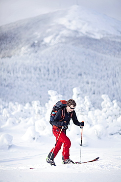 A backcountry skier skins along the snowfields on Burnt Mountain, Maine.