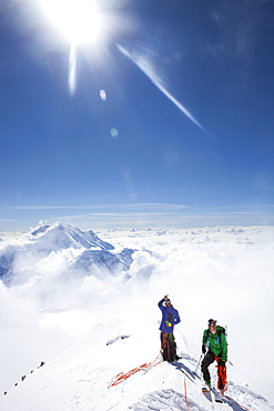 Climbers and rangers Dave Weber and Tom Ditolla are on a snow ridge of the West Rib high on Mount McKinley. Dave is pointing to the summit, Mount Hunter is seen in the background.