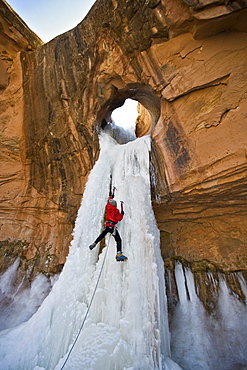 A man ice climbing a frozen waterfall through a sandstone arch in Utah.