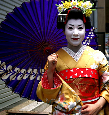 A Geiko (Geisha) poses on a street in Kyoto, Japan.