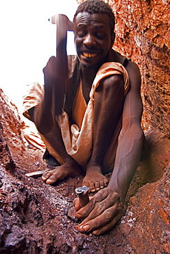 A gold miner works in a shaft using hand tools in Sudan.