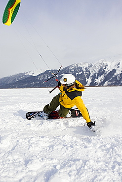 A mid adult man enjoys the outdoors while snow kiting in Alaska.