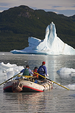Raft negotiating icebergs in a lake in Alaska, United States.