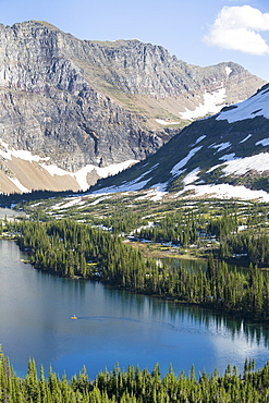 A man stand up paddle boards (SUP) on a calm Hidden Lake in Glacier National Park.