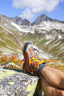 A male hiker takes a rest during the Glocknerrunde, a 7 stage trekking from Kaprun to Kals around the Grossglockner, the highest mountain of Austria.