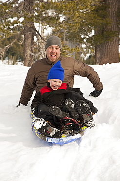 Father and son sledding in fresh snow