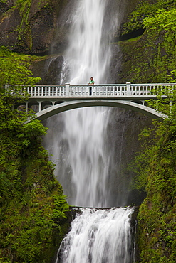 A man stands on the Benson Bridge in front of Multnomah Falls, a 542-foot waterfall located in the Columbia River Gorge, Oregon.