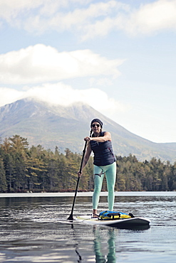 A young woman paddle boards on a pond in Maine.