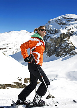 Famale sking doing snowsports on a snow mountain in Val D'Isere with an orange jacket on a sunny day