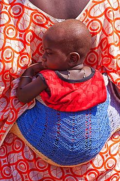 African bedik woman carrying a child while doing housework,  ziguinchor, casamance, Senegal, Africa