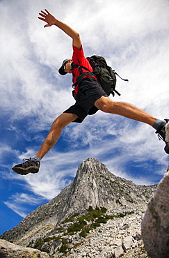 Low Angle View Of Male Backpacker Jumping In British Columbia