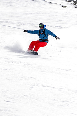 Snowboarder Making A Turn In Fresh Snow Powder