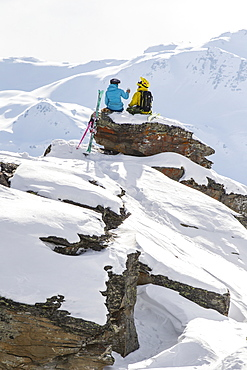 Two Skiers Resting And Drinking Water After A Good Ski Run