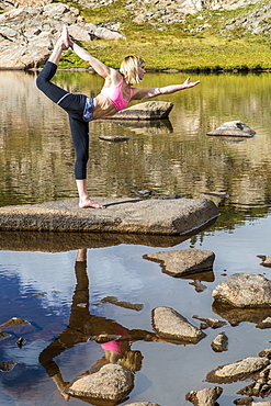 An Young Athlete Woman Practices Yoga On A Lake