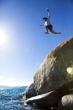 Man Jumping On Rock Into The River At Sand Harbor State Park