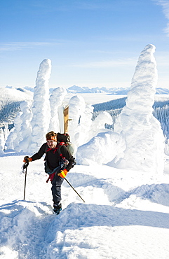 Male Skier Hiking On Snowy Landscape In Whitefish, Montana, Usa