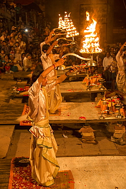 Hindu priests raise large aarti lamps during Ganga Aarti at Dashaswamedh ghat, Varanasi, Uttar Pradesh, India
