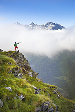 Hike on steep ridge pointing with hiking pole with mountain range in background