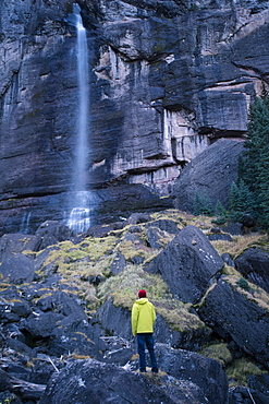 Young male stands at the base of Bridal Veil Falls in Telluride Colorado