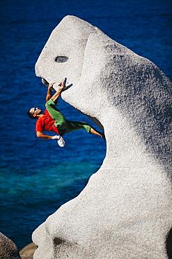 Man climbing on rock near sea, CapoTesta, Sardinia, Italy