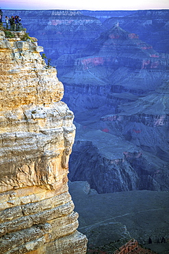 Tourists gather on the South Rim of the Grand Canyon at a viewpoint to view the sunset.