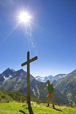 A male hiker is walking towards a wooden cross on a mountain meadow in the Val d'Anniviers in the Swiss Alps. The sun is shining bright, temperatures are high. This is halfway the Haute Route, a classic hike between Chamonix in France and Zermatt in Switzerland. For fit hikers it takes ten days.