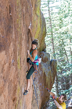 A strong female rope climber makes beginning moves on a difficult line in Colorado